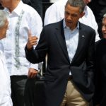 Barack Obama, Otto Perez Molina standing next to a man in a suit and tie