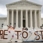 A group of people in front of United States Supreme Court Building