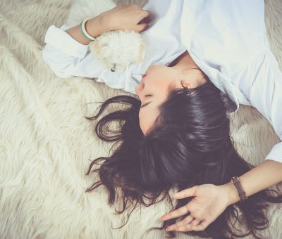 A Girl sleeping on a bed with pet Dog